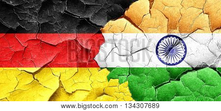 German flag with India flag on a grunge cracked wall