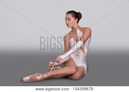 the ballerina sits on the floor and ties pointes