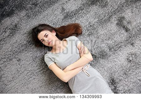 Beautiful girl lying on grey floor