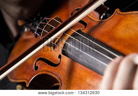 Detail a violinist playing his instrument. Classic music concept.
