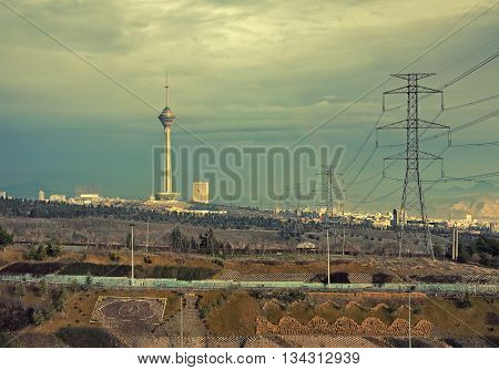 Beautiful rainbow beside Milad Tower and power transmission lines above hillside against overcast sky of Tehran in autumn edited with vintage filter.