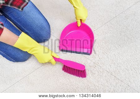 Female hands in yellow gloves sweeping a carpet brush.