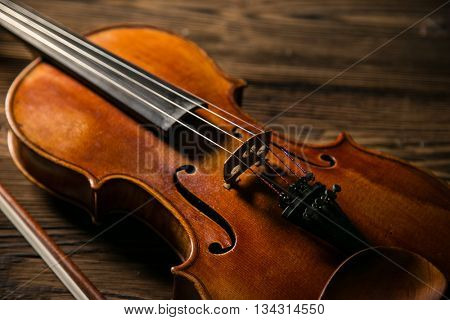 Classic music violin vintage in wooden background, close-up.