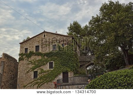 GIRONA SPAIN - JULY 17 2013: In the historic center of Girona. Old house twined with green leaves. Well preserved since the Middle Ages the historic core of the city attracts a significant number of tourists