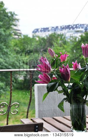 Purple Liliums in a vase on a balcony