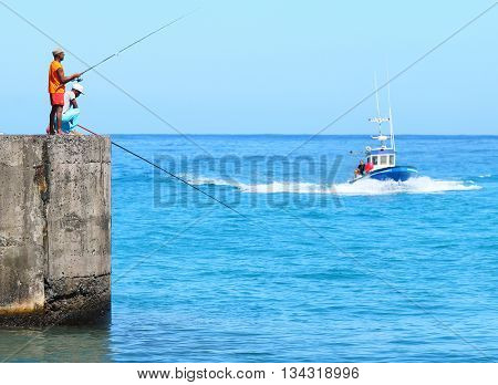 SAINT-PAUL, REUNION ISLAND, FRANCE - NOVEMBER 11, 2015: Unidentified african fishermens catching a fish in harbor. Traditional leisure activity for natives on Reunion.