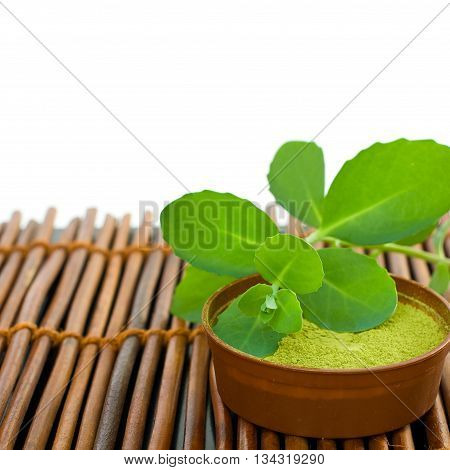 Spa background with mud and green leaves on bamboo mat