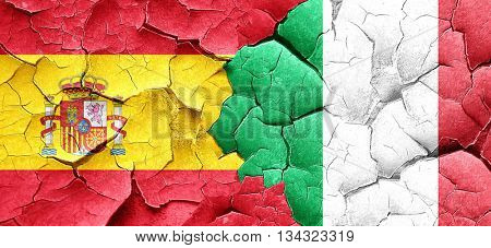 Spanish flag with Italy flag on a grunge cracked wall