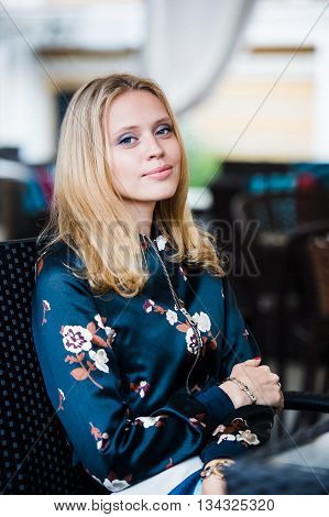 Young gorgeous European woman with pretty face thinking about something while sitting with laptop computer in cafe bar, dreamy beautiful female using portable net-book during work break in coffee shop.