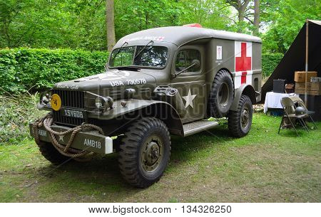 Silsoe, Bedfordshire, England - May 30, 2016: World War 2 American Ambulance with Red Cross parked in woods..