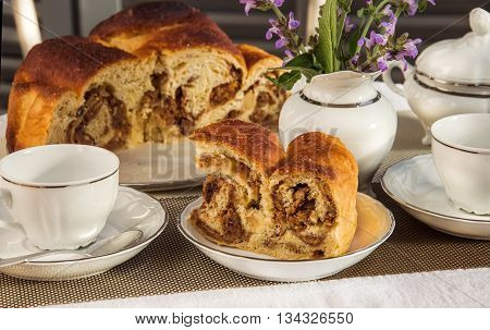 Typical italian flavorous home baked cake La Gubana with sophisticated stuffing (hazelnuts fruit chocolate walnut raisins honey etc.) with purple flowers of salvia on the table covered for breakfast. Traditionally bake for Christmas and Easter.