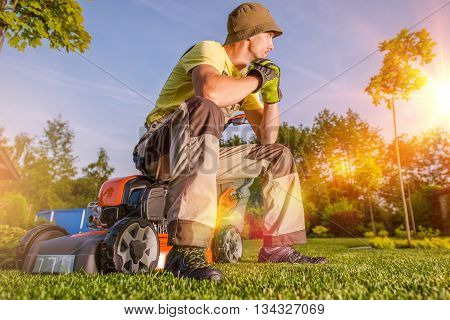 Garden is My Hobby and My Passion. Passionate Caucasian Men Watching His Beautiful Garden While Seating on His Grass Mower After Hard Working Day. Garden Lover.