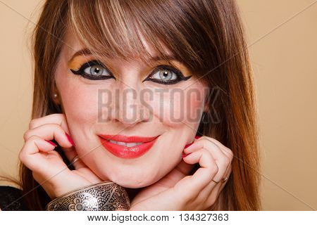 Closeup portrait young attractive orient eastern girl with perfect make-up. Woman with fashionable accessories bijouterie armlet. Beauty makeup eye liner red lips.