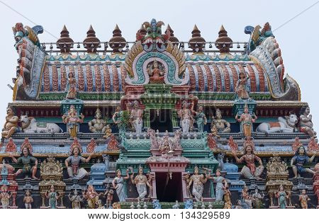 Chettinad India - October 17 2013:The Kalasha the top of Gopuram at Shiva temple in Kottaiyur. Loaded with Hindu-themed colorful statues with Lakshmi on top and center.