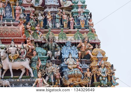 Chettinad India - October 17 2013:Detail of the Shiva temple gopuram at Kottaiyur shows Shiva and Parvati residing on Himalayan Kailash mountain on top of multi-headed Ravana. Combination of multiple colorful statues on Shiva temple gopuram.