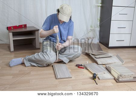 Assemble wooden furniture woman putting together self assembly furniture.
