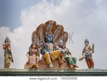 Chettinad India - October 17 2013:Detail of the Shiva temple at Kottaiyur shows Lord Vishnu Devi Lakshmi and Devi Bhu sitting on coils of five-headed cobra Shesha. Called Sheshanarayana. Other Vishnu avatar in photo: Hayagriva