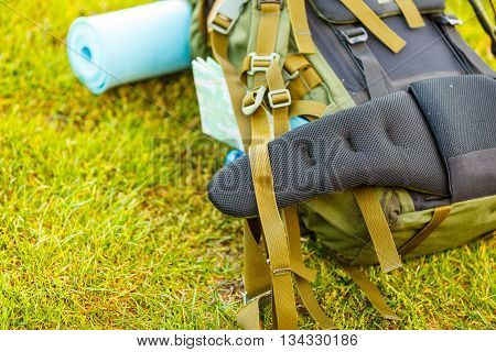 Hiking backpack camping and mountain exploring tourist equipment outdoor on grass. Adventure summer tourism active lifestyle