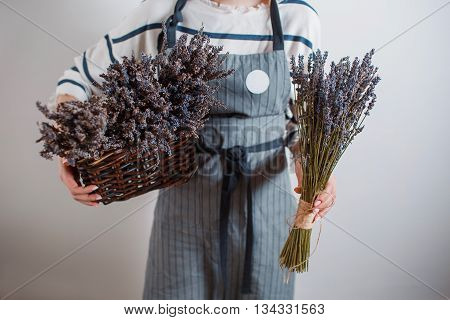 Beautiful girl on the lavender field. Young woman collects lavender in a basket. Summer