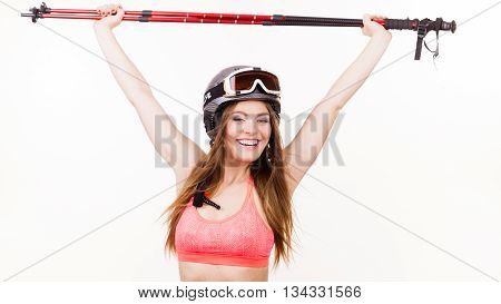 Woman lifting skiing poles. Young skier girl wearing helmet goggles. Winter sport lifestlye relax fitness concept.