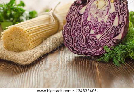 Pasta with cabbage and greens on the wooden table for dinner