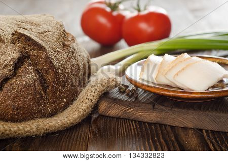 Baked bread with fat tomatos onion and pepper on wooden table background for lunch