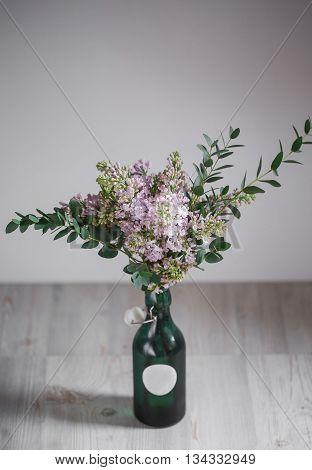 Lilac flower in a green vase on a wooden background