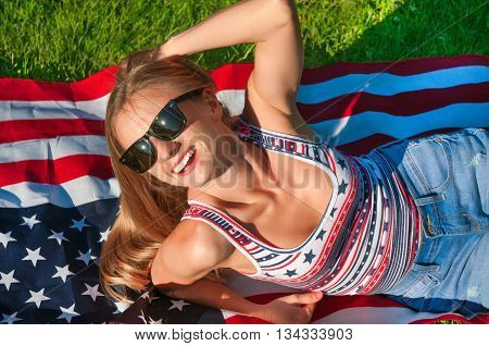 Young happy patriot girl on the american united states flag