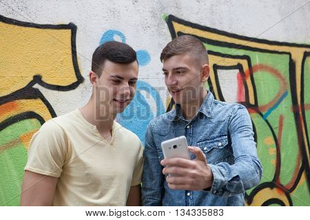 Friends watching the phone in the street with a painted wall graffiti background