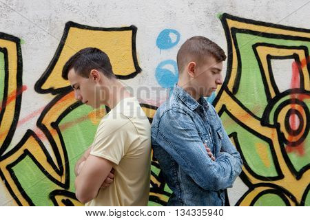 Teenage friends angry with wall graffiti background