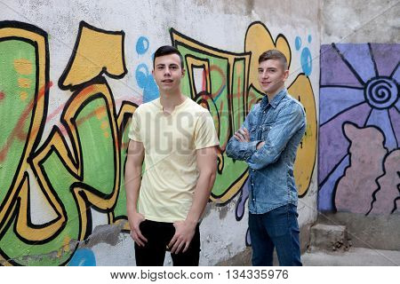 Two teenage boys in the street with graffiti background