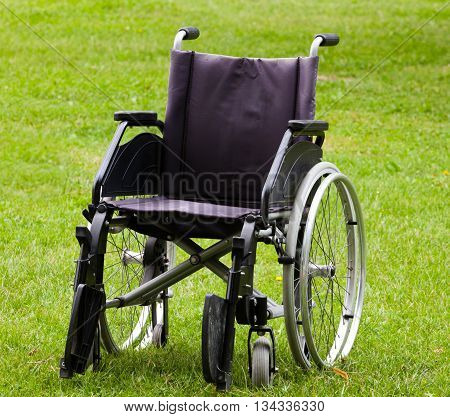 Empty wheelchair on grass field in the park.