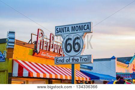 Santa Monica, CA, USA - January 11, 2016: Santa Monica California pier at sunset 66 sign. The roller coaster at the amusement park souvenirs