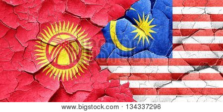 Kyrgyzstan flag with Malaysia flag on a grunge cracked wall