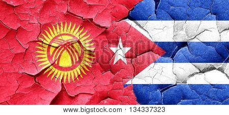 Kyrgyzstan flag with cuba flag on a grunge cracked wall