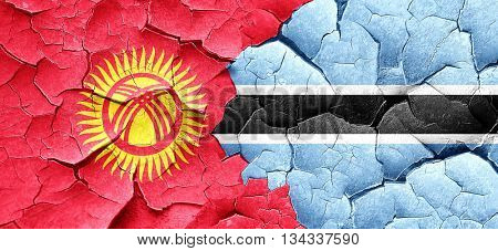 Kyrgyzstan flag with Botswana flag on a grunge cracked wall