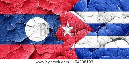 Laos flag with cuba flag on a grunge cracked wall