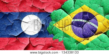 Laos flag with Brazil flag on a grunge cracked wall