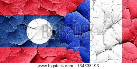 Laos flag with France flag on a grunge cracked wall