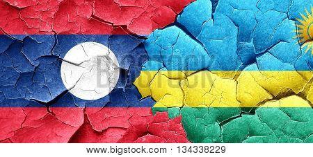 Laos flag with rwanda flag on a grunge cracked wall