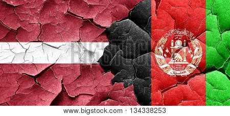 Latvia flag with afghanistan flag on a grunge cracked wall