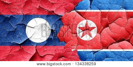 Laos flag with North Korea flag on a grunge cracked wall