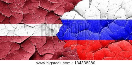 Latvia flag with Russia flag on a grunge cracked wall
