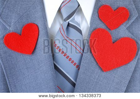 Close up of man's chest dressed in a suit jacket in grey with red black and grey striped tie and a white shirt. Heart shaped felt cutouts on the lapels indicate love for Dad great for Father's Day