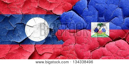 Laos flag with Haiti flag on a grunge cracked wall