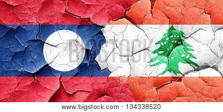 Laos flag with Lebanon flag on a grunge cracked wall