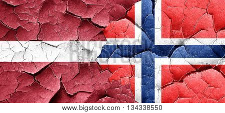 Latvia flag with Norway flag on a grunge cracked wall