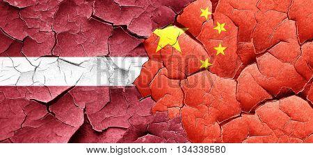Latvia flag with China flag on a grunge cracked wall