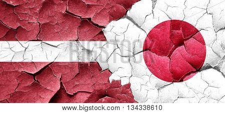 Latvia flag with Japan flag on a grunge cracked wall