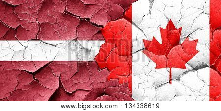 Latvia flag with Canada flag on a grunge cracked wall
